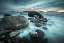 Rocks In Frozen Sea During Sunset