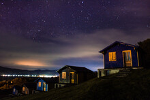 Illuminated Houses Against Sky At Night