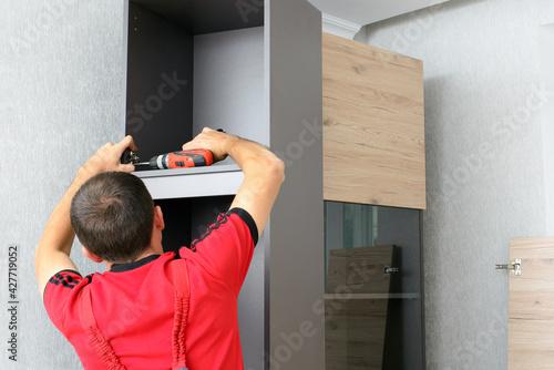 Obraz Assembling furniture from chipboard, using a cordless screwdriver - fototapety do salonu