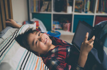 Portrait Of Happy Boy With Digital Tablet At Home
