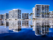 Reflection Of Buildings In Lake Against Blue Sky