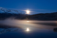 Picturesque Misty Moonlit Night On Lake Dzhangyskol And Reflection In The Water. Russia, Altai Republic,