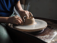Woman Starts To Create A Ceramic Cup On The Pottery Wheel. Working With Clay On Potter's Wheel.