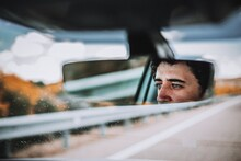 Reflection Of Man In Rear-view Mirror Of Car