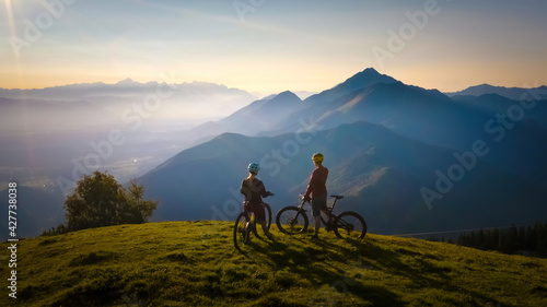 Slika na platnu Two females on mountain bikes talking and looking at beautiful sunset