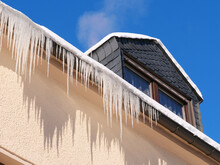 Low Angle View Of Building Against Blue Sky, Icicles On A House