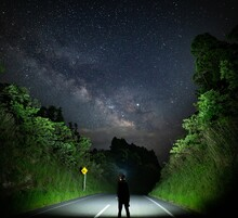 Rear View Of Man On Road Against Sky At Night