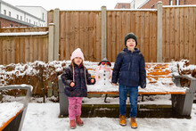 Portrait Of Boy And Girl Standing In Snow