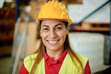 Portrait Of A Happy Adult Caucasian Working Woman Looking At The Camera Inside A Warehouse Wearing A Hard Hat And Safety Clothing - Focus On The Face