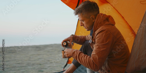 Obraz man traveler sitting at camp tent and pouring warm coffee from thermos in mug - fototapety do salonu