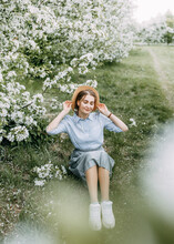 Beautiful Pretty Young Woman Walks Enjoying The Aroma Of Blooming Apple Flowers In A Spring Park
