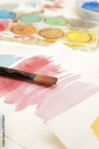 Tela Watercolor paints palette, brushes and papers on table