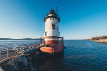Lighthouse In Sea Against Clear Blue Sky
