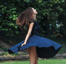 Attractive Sexy Happy Young Girl With Navy Dress Jumps On The Lawn.