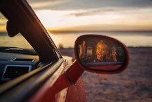 Autumn Road Trip, Freedom And Family Traveler. Pretty Girl Sitting In The Car On The Bank Of Sea, Rest And Leisure, Looking At Beautiful Sunset After Rain, Drops On Windshield, Fall Outdoor Lifestyle