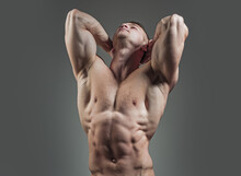 Muscular Man Athlete. Bodybuilder With Sexy Muscular Athletic Body With Bare Torso And Strong Belly With Six Packs Or Abs In Studio On Grey Background.