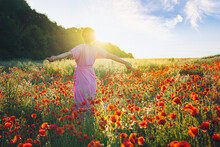 Backview Happy Young Woman In A Pink Dress With Raised Arms Relaxing In Red Poppies Flowers Meadow In Sunset Light. A Simple Pleasure For Mental Health. Nature Relaxation. Selective Focus. Copy Space
