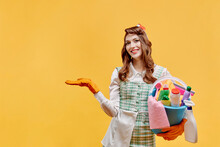 A Happy Cleaning Lady Holds A Bucket Of Tools And Points Her Hand At A Copy Of The Space. A Bottle Of Household Chemicals And Cleaning Products. Pin-up Style. Yellow Background.