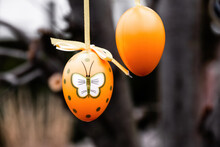 Closeup Shot Of Two  Orange Easter Eggs Hanging On The Tree,  Butterfly Painted On One Of Them