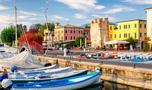 Bardolino, Italy, 10/28/2019: Boats In Old Town Port Of Bardolino And Tourists Walking And Sitting In Restaurants. The Town Is A Popular Holiday Destination In Garda Lake District.