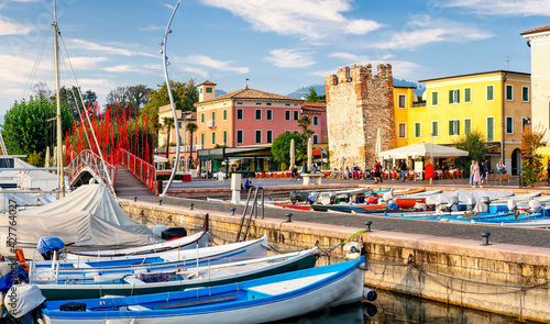 Fotografie, Obraz Bardolino, Italy, 10/28/2019: Boats in old town port of Bardolino and tourists walking and sitting in restaurants