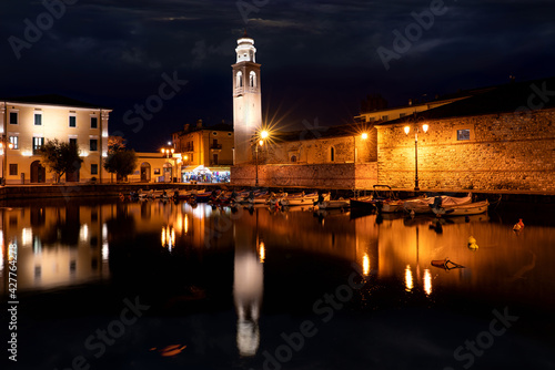 Foto Boats in old town port of Lazise at twilight