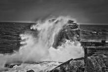 Waves Splashing On Rocks Against Sea