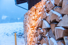 Full-sized Side View Of Freshly Beaten, Stacked On A Barn And Snow-covered Firewood In Snowfall.