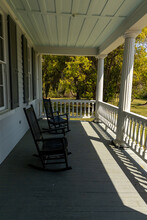 Two Rocking Chairs On Large White House Porch Overlooking Peaceful Yard