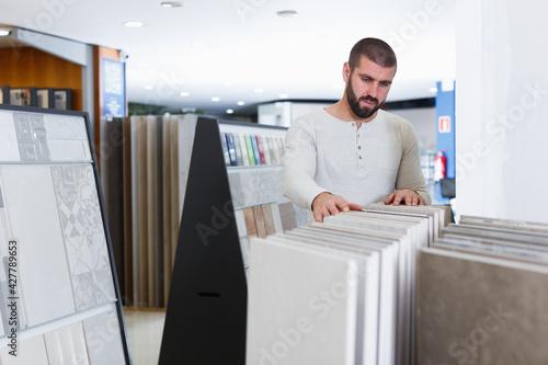 Fotografie, Obraz Portrait of man customer choosing ceramic tile in domestic shop
