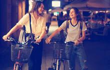 Two Friends Happy Smiling Young Women Walking With Bicycles At Night European City Using Rental Transport