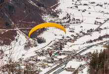 Bird View Of Linthal, In The Valley Of Glarus, Switzerland, With A Paraglider Gliding Towards The Town