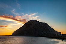Scenic View Of Morro Bay Rock And Ocean Against Sky During Sunset.