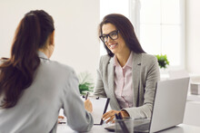 Friendly Smiling Human Resources Manager Conducting Job Interview With Applicant In Office. Woman Hired Job Seeker Signing Contract After Successful Negotiation With Company HR Employer In Office