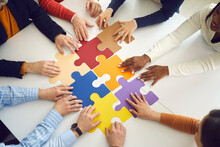 Solidarity, Strategy Collaboration, Business Workflow And Communication Research Concept. Diverse Multiethnic Office People Team Assembling Jigsaw Puzzle Pieces Holding Hands On Table Top View