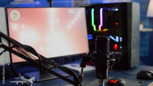 Obraz Game is loading on display of RGB professional powerful computer and stream chat is prepared for virtual tournament. Streaming professsional microphone in empty gaming home studio with neon lights. - fototapety do salonu