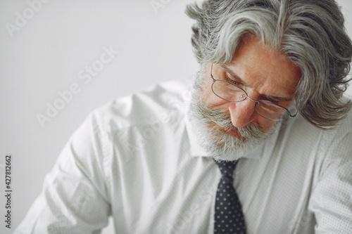 Fotografie, Obraz Handsome pensive mature businessman sitting in the office
