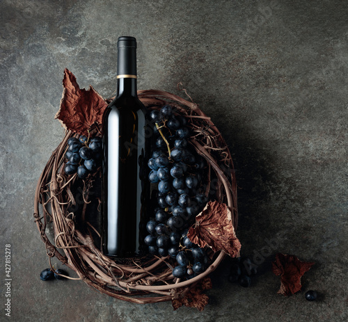 Fototapeta Bottle of red wine with grapes and dried vine leaves on an old stone background. obraz na płótnie