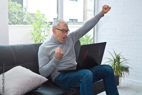man raising arms in success or victorious sign in front of laptop - fototapety na wymiar