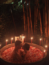 Couple Lies In A Round Bath With Fruits