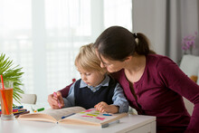 Cute Preschool Child, Blond Boy, Filling Some Homework In A Work Book And Coloring, Mother Helping Him