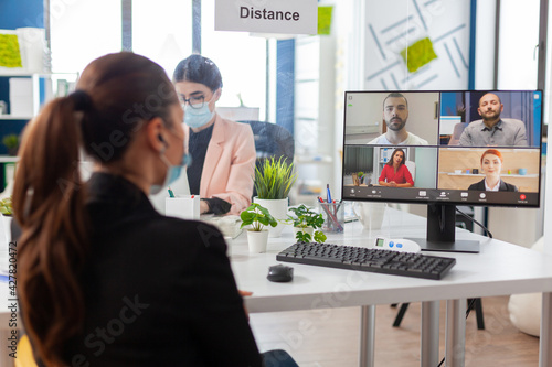 Obraz Back view of woman talking with team during remote video conference in new normal office in timp of global pandemic with coronavirus, keeping social distancing wearing face mask. - fototapety do salonu