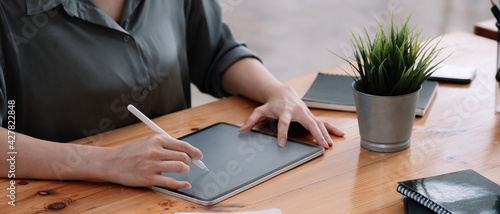 Obraz Close up woman hands drawing on digital tablet with electronic pen. Freelancer designer working remotely. Close-up photo. - fototapety do salonu