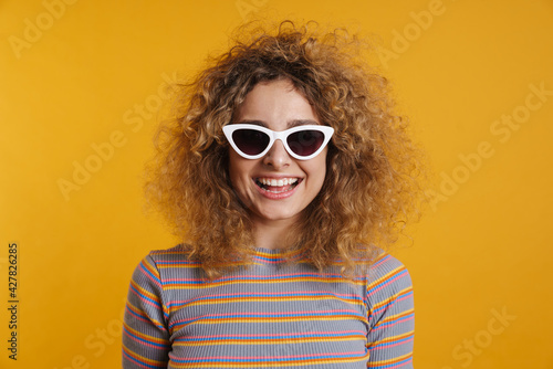 Fototapeta Happy young casual woman with fizzy hairstyle standing obraz