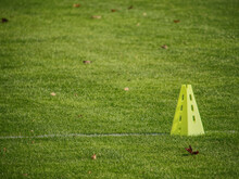 Yellow Triangles Used As Soccer Training Equipment On Green Grass Field