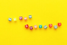 Happy Birthday Inscription Made Of Colorful Cubes Beads On Yellow Background