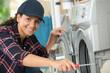 young woman repairing a washing machine