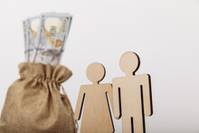Dollar Money Bag With Wooden Figures Of People On White Background. Family Savings Concept. Close-up