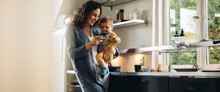 Mother Using Phone While Carrying Baby In Kitchen