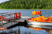 Orange Catamarans On Lake Moored At The Pier. Pleasure Boats With Life Jackets.